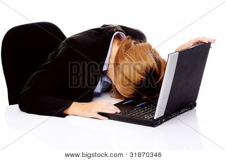 frustrated business woman with stress headache sitting at her desk with computer isolated on white.