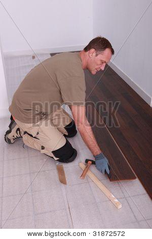 Man at home laying wooden flooring