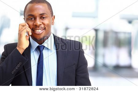 Smiling Businessman am Telefon in seinem Büro