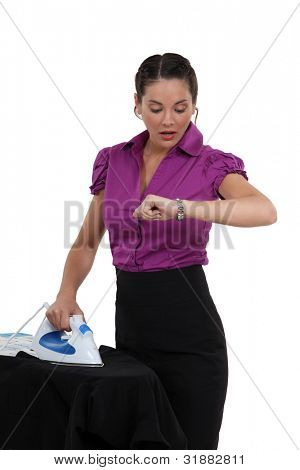 Woman ironing and watching the time go by