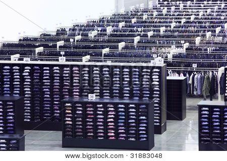 Tienda de ropa grande, muchas filas con ganchos, estantes de camisas