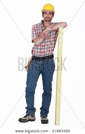 carpenter with arm resting on plank