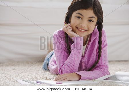 Young Hispanic girl doing homework on the floor