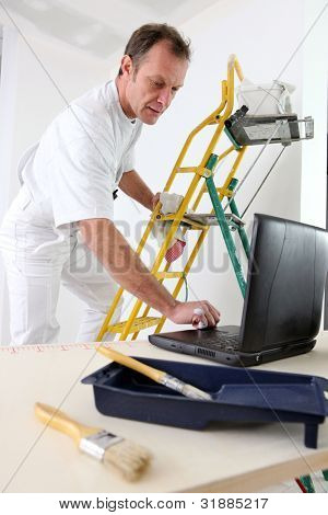 Painter taking quick break to reply to e-mail