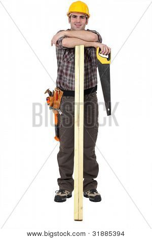 carpenter with arms resting on lumber holding handsaw