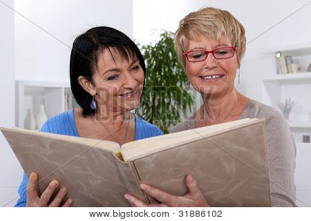Two women looking through photo album