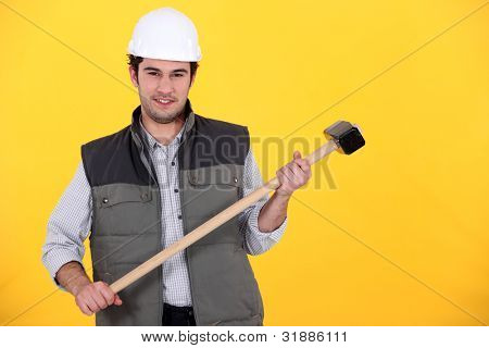 craftsman with hammer against yellow background