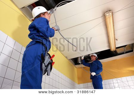 Two electrician working on ceiling wiring