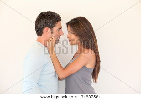Woman pulling on boyfriend's cheeks
