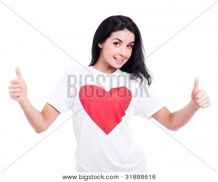 excited young woman wearing a T-shirt with a big red heart and  and showing two thumbs up, isolated against white background