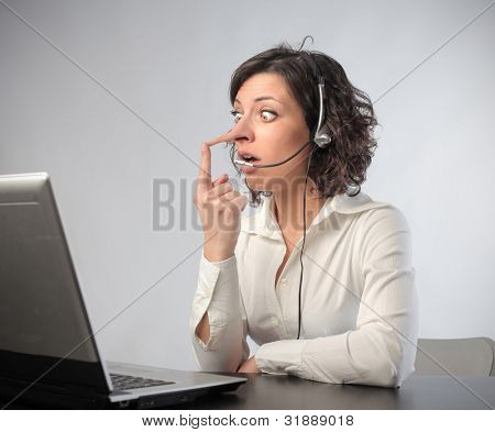 Young receptionist with long nose and astonished expression in front of a laptop
