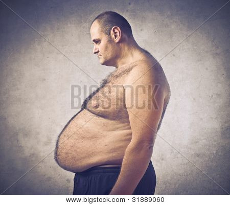 Sad overweight man looking at his belly