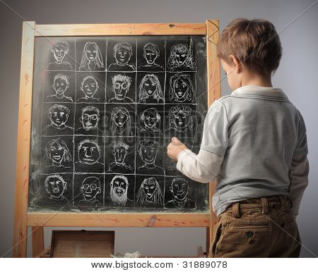 Child drawing some portraits of a blackboard