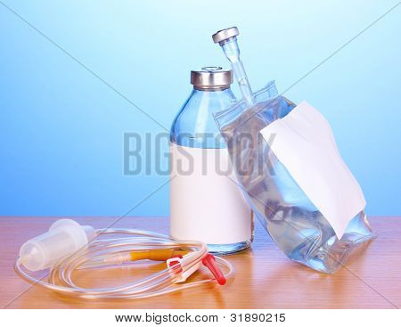 Bottle and bag of intravenous antibiotics and plastic infusion set on wooden table on blue background