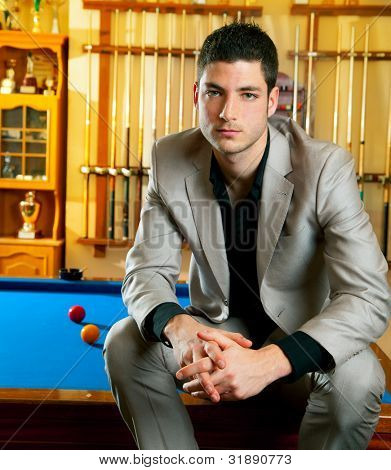 handsome man with suit sitting posing in billiard pool in club