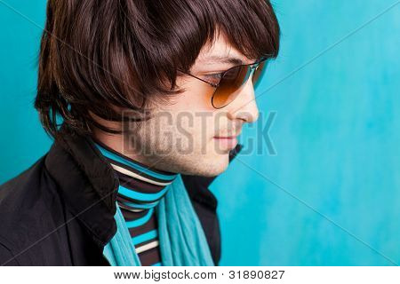 british indie pop rock look retro hip young man with sunglasses on blue
