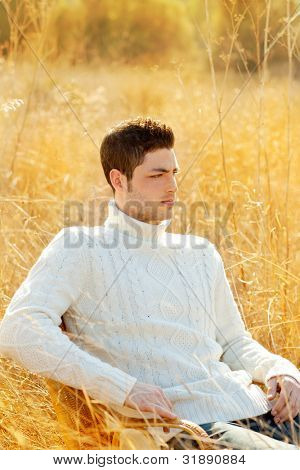 Autumn winter man portrait in outdoor dried grass field with turtleneck sweater