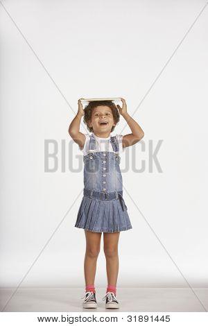 Portrait of girl balancing book on head