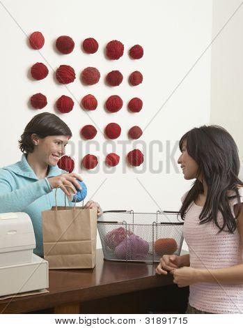 Woman buying yarn in yarn store