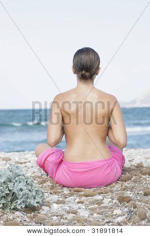 Jovem mulher semi-nua meditando na praia
