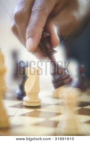 Close up of hand moving chess piece