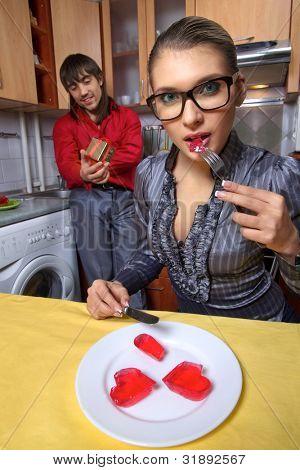 Happy young woman eating red jelly hearts and her boyfriend giving present on kitchen