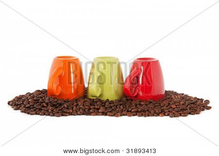 Colorful coffee mugs standing on beans isolated over white background