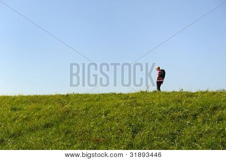 Elderly man is walking alone at the Dutch dike