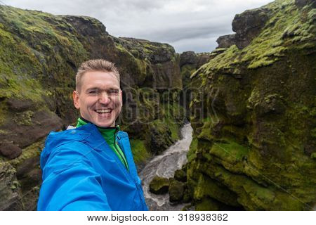poster of Young Smiling Man With River And Green Canyon On Background Takes A Selfie. Concept Of Freedom Movem