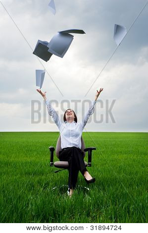 smiley businesswoman throwing away documents at the field