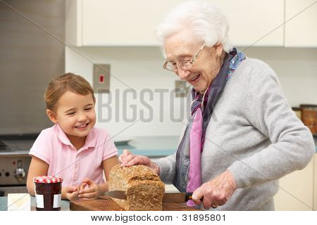 Grandmother and granddaughter preparing food in kitchen
