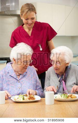 Senior women with carer enjoying meal at home