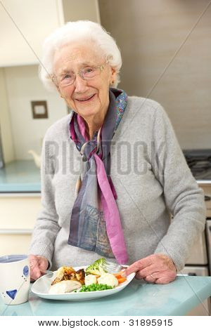 Senior woman enjoying meal in kitchen