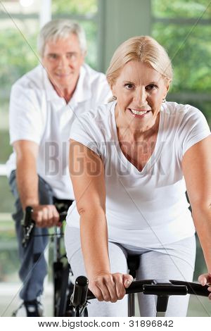 Happy senior people exercising on spinning bikes in gym
