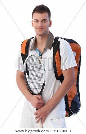 Young tennis player going to training, holding backpack and tennis racket, smiling.
