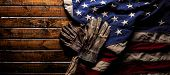 Old and worn work gloves on large American flag - Labor day background poster