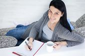 Smiling young girl drinking tea and making note , domestic life, poster