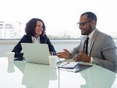 Happy Coworkers Discussing New Business Software. Business Man And Woman Sitting At Meeting Table Wi poster