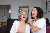 Excited Mother And Daughter Laughing. Cheerful Senior Mother And Adult Daughter Sitting Together On  poster