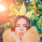 Modern Fashion Outfit. Gorgeous Pretty Woman In Furry Coat Fallen Leaf On Head As Crown. Trendy Outf poster
