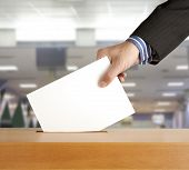foto of poll  - Hand putting a voting ballot in a slot of box - JPG