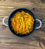 Thinly Cut Thin Strips Of Carrots. Fried And Stewed Carrot Spaghetti In A Pan On A Wooden Table poster