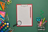 Clipboard with blank sheet, shopping trolley and stationery accessories on green background. Top vie poster