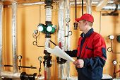 stock photo of pressure vessel  - maintenance repairman engineer of heating system equipment in a boiler house - JPG