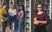 Student Lifestyle. Female Student With Glasses Posing In Front Of Group Of Students, Library Interio poster