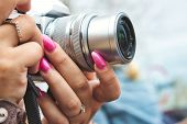 Close-up Of A Digital Camera Being Used By A Woman With Painted Fingernails poster