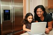 pic of mother daughter  - Woman in her kitchen with daughter on the computer - JPG