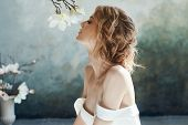 Beautiful Slender Blonde Girl Sitting On The Floor In Long White Dress. Portrait Woman With Flower I poster