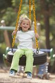 stock photo of tire swing  - Portrait of girl swinging on tire swing - JPG