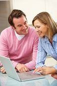 Mature couple using laptop in domestic kitchen poster